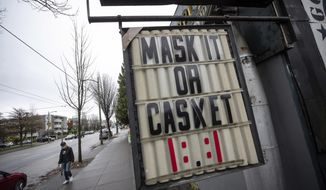 A sign regarding mask use to help curb the spread of COVID-19 hangs outside a business in Vancouver, British Columbia, Sunday, Dec. 6, 2020. (Darryl Dyck/The Canadian Press via AP)