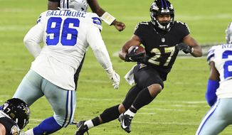 Baltimore Ravens running back J.K. Dobbins (27) runs the ball against Dallas Cowboys defensive tackle Neville Gallimore (96) during the second half of an NFL football game, Tuesday, Dec. 8, 2020, in Baltimore. (AP Photo/Terrance Williams)