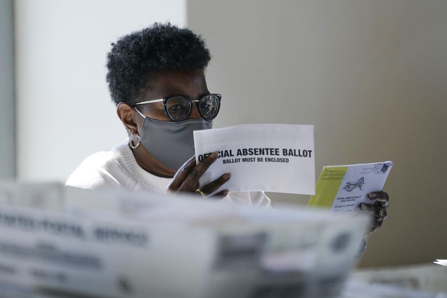 A worker at the Fulton County Board of Registration and Elections works to process absentee ballots at the State Farm Arena Monday, Nov. 2, 2020, in Atlanta. (AP Photo/John Bazemore)