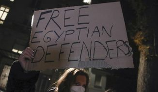 """A woman holds a placard as she stages a protest against the Egyptian President Abdel-Fattah el-Sissi by the National Assembly in Paris, Tuesday, Dec. 8, 2020. French President Emmanuel Macron acknowledged Monday """"disagreements"""" with Egyptian President Abdel-Fattah el-Sissi over human rights, but said it will not prevent France from reaching economic and defense deals with the North African country, which has seen the heaviest crackdown on dissent in its modern history. (AP Photo/Michel Euler)"""