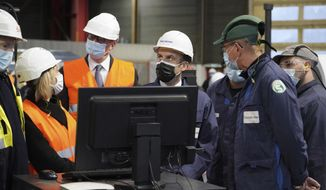 French President Emmanuel Macron, center, visits the Framatome nuclear reactor production site in Le Creusot, France, which the government holds up as an example of industry that serves both civilian and military needs, Tuesday, Dec. 8, 2020. Macron wants to stress that nuclear energy is central to France's energy transition and says it emits less than wind or solar. (AP Photo/Laurent Cipriani, Pool)