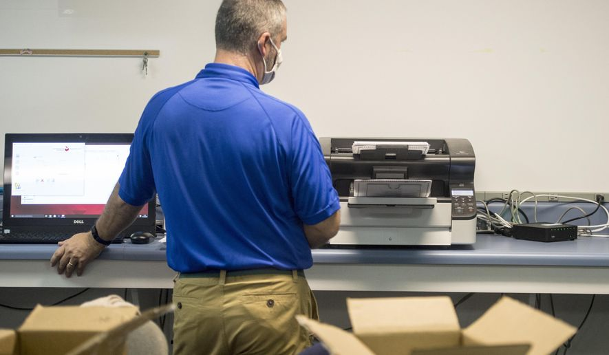 Board of Elections Assistant Director Travis Doss waits for a machine to finish counting absentee ballots during the Georgia presidential election recount at a Richmond County elections facility in south Augusta, Ga., Monday morning, Nov. 30, 2020. (Michael Holahan/The Augusta Chronicle via AP)