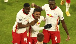 Leipzig's Justin Kluiver, center, celebrates after scoring his side's third goal during the Champions League group H soccer match between RB Leipzig and Manchester United at the RB Arena in Leipzig, Germany, Tuesday, Dec. 8, 2020. (AP Photo/Matthias Schrader)