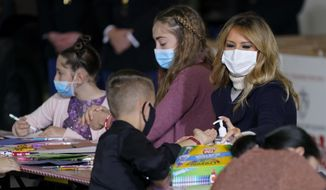 First lady Melania Trump offers hand sanitizer to a child as she participates in the U.S. Marine Corps Reserve's Toys for Tots Drive at Joint Base Anacostia-Bolling in Washington, Tuesday, Dec. 8, 2020. (AP Photo/Patrick Semansky)