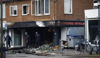 People inspect the debris after an explosion in Aalsmeer, near Amsterdam, Netherlands, in the early hours of Tuesday morning Dec. 8, 2020. Two Polish supermarkets in the Netherlands were badly damaged by explosions Tuesday but no injuries were reported police said. (AP Photo/Peter Dejong)