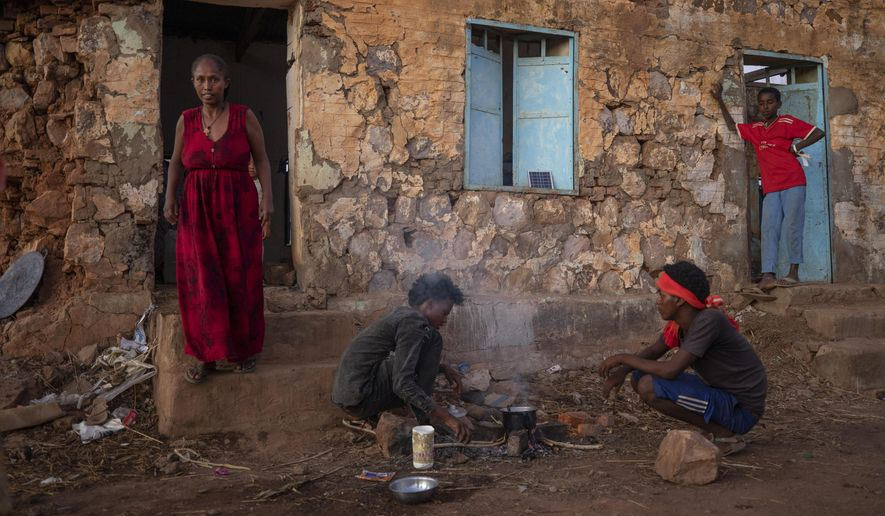 Tigrayans who fled the conflict in Ethiopia's Tigray region, start wood fires to prepare dinner, in front of their temporary shelters at Umm Rakouba refugee camp in Qadarif, eastern Sudan, Monday, Dec. 7, 2020. (AP Photo/Nariman El-Mofty)