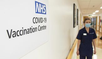 Signs for the COVID-19 Vaccination Centre at the Royal Free Hospital in London, Monday Dec. 7, 2020, as preparations are made ahead of the coronavirus vaccination programme from Tuesday. (Dominic Lipinski/Pool via AP)