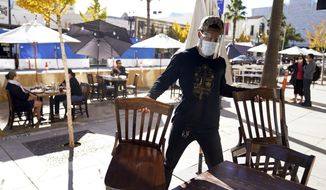 In this Tuesday, Dec. 1, 2020, file photo, general manager Damien Williams prepares outdoor seating at Settebello Pizzeria Napoletana in Pasadena, Calif. (AP Photo/Marcio Jose Sanchez, File)