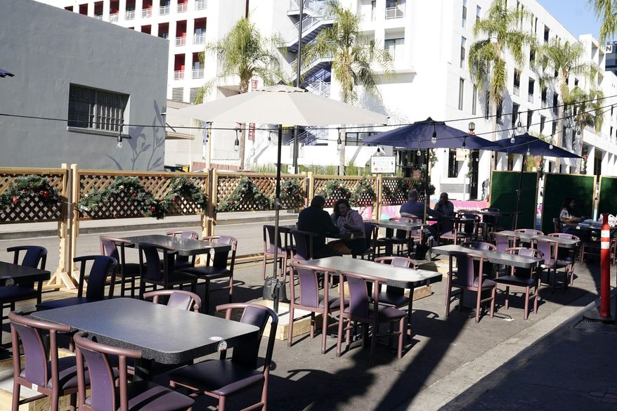 In this Dec. 4, 2020, file photo, empty tables are seen outside of a restaurant set up for outdoor dining in Burbank, Calif. Five California legislative assembly members dined together outdoors Monday, Dec. 8, 2020, despite surging coronavirus case levels that have triggered stay at home orders for much of the state's population. State rules are silent as to how many households can dine together outdoors at restaurants, but health officials have implored people to limit outside gatherings to no more than three households.(AP Photo/Marcio Jose Sanchez, File)  **FILE**