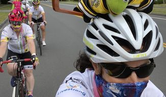 """In this July 31, 2020 photo, Pan-Mass Challenge bike rider Celia Donatio, right, cycles with her teammates through Needham, Mass. """"Team Kermit"""" raised close to $554,000 for Dana Farber Cancer Research. PMC founder Billy Starr knew he wouldn't be able to get 10,000 people together this summer for the annual cross-state bike ride that has raised more than $700 million for cancer research. But he also knew he couldn't take the year off. While other events in the $1.4 billion participatory fundraising field shut down during the coronavirus outbreak, the PMC delivered $50 million for the Dana-Farber Cancer Institute. (Photo by Celia Donatio via AP)"""