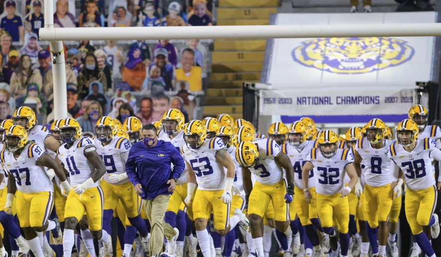 LSU head coach Ed Orgeron leads his team on the field before an NCAA college football game against Alabama in Baton Rouge, La., Saturday, Dec. 5, 2020. (AP Photo/Matthew Hinton)
