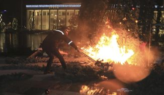 A Christmas tree is on fire near the Prime's Minister office during clashes in Tirana, Albania , on Wednesday, Dec. 9, 2020. Clashes have broken out in Tirana during a protest by hundreds of Albanians demanding the interior minister's resignation over the fatal police shooting of a 25-year-old man who had breached a coronavirus-linked curfew. (AP Photo/Hektor Pustina)