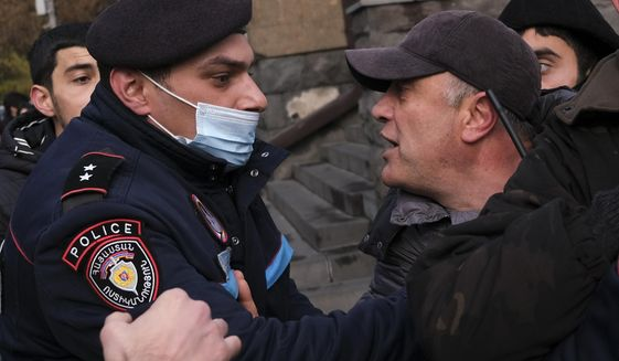 A police officer tries to detain demonstrators during a rally demanding the resignation of the country's prime minister over his handling of the conflict with Azerbaijan over Nagorno-Karabakh in Yerevan, Armenia, Tuesday, Dec. 8, 2020.Armenian opposition politicians and their supporters have been calling for Prime Minister Nikol Pashinyan to step down ever since he signed a peace deal that halted 44 days of deadly fighting over the separatist region, but called for territorial concessions to Azerbaijan. (AP Photo/Hrant Khachatryan)