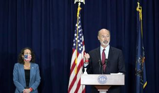 Pennsylvania Gov. Tom Wolf, right, speaks as Pennsylvania Secretary of State Kathy Boockvar, left, looks on during a news conference offering updates regarding the counting of ballots in the 2020 general election, Wednesday, Nov. 4, 2020, in Harrisburg, Pa. (AP Photo/Julio Cortez)