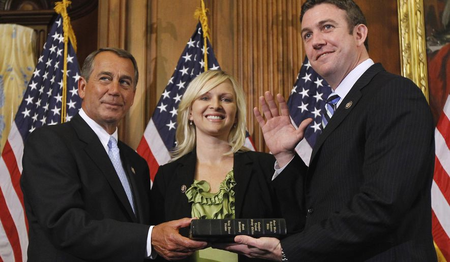 FILE - In this Jan. 5, 2011, file photo, then House Speaker John Boehner of Ohio, left, administers the House oath to Rep. Duncan Hunter, R-Calif., as his wife, Margaret Hunter, looks on during a mock swearing-in ceremony on Capitol Hill in Washington. Margaret Hunter has filed for divorce from former Rep. Duncan Hunter on Nov. 20, 2020, in San Diego Superior Court according to online records.  Both were convicted of corruption and prosecutors had said that the lawmaker had used campaign funds on extramarital affairs. (AP Photo/Alex Brandon, File)