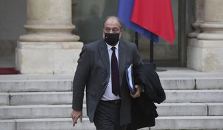 """French Justice Minister Eric Dupond-Moretti leaves the weekly Cabinet meeting at the Elysee Palace in Paris, Wednesday, Des. 9, 2020. A draft law aimed at arming France against Islamist radicalism was unveiled at Wednesday's weekly Cabinet meeting, a measure promoted by President Emmanuel Macron to rout out what he calls """"separatists"""" undermining the nation. (AP Photo/Michel Euler)"""