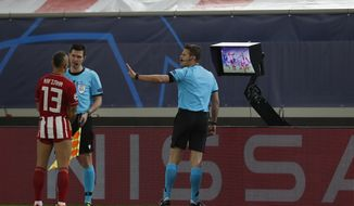Referee Felix Brych, right, prepares to check the VAR screen during the Champions League, group C soccer match between Olympiacos and FC Porto at Georgios Karaiskakis stadium in Piraeus port, near Athens, Wednesday, Dec. 9, 2020. (AP Photo/Thanassis Stavrakis)
