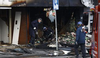 Forensic experts inspect the debris after an explosion in Aalsmeer, near Amsterdam, Netherlands, Tuesday morning Dec. 8, 2020.  Two Polish supermarkets in the Netherlands were badly damaged by explosions early Tuesday but no injuries were reported police said. (AP Photo/Peter Dejong)