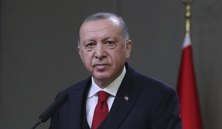 """Turkey's President Recep Tayyip Erdogan speaks to reporters before departing for a visit to Azerbaijan, in Ankara, Turkey, Wednesday, Dec. 9, 2020. Erdogan brushed off possible European Union sanctions against Turkey on Wednesday, saying they would not affect his country. Erdogan also accused the EU of acting """"dishonestly"""" toward Turkey and of failing to keep its promises.(Turkish Presidency via AP, Pool)"""