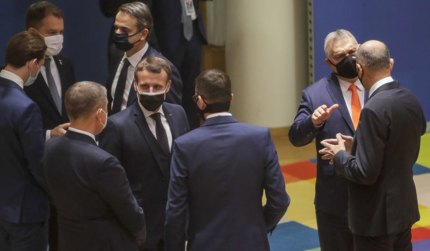 French President Emmanuel Macron, center, speaks with Romania's President Klaus Werner Ioannis, third left, and Poland's Prime Minister Mateusz Morawiecki, center right, during a round table meeting at an EU summit in Brussels, Thursday, Dec. 10, 2020. European Union leaders meet for a year-end summit that will address anything from climate, sanctions against Turkey to budget and virus recovery plans. Brexit will be discussed on the sidelines. (Olivier Hoslet, Pool via AP)