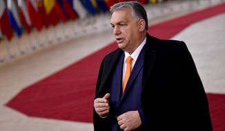 Hungary's Prime Minister Viktor Orban speaks as he arrives for an EU summit at the European Council building in Brussels, Thursday, Dec. 10, 2020. European Union leaders meet for a year-end summit that will address anything from climate, sanctions against Turkey to budget and virus recovery plans. Brexit will be discussed on the sidelines. (John Thys, Pool via AP)