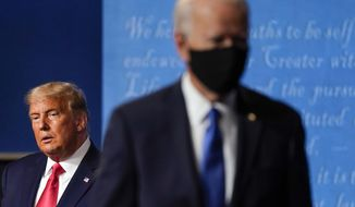 FILE - President Donald Trump, left, remains on stage as then-Democratic presidential candidate former Vice President Joe Biden, right, walks away Thursday, Oct. 22, 2020, at Belmont University in Nashville, Tenn. President Trump's extraordinary effort to overturn Joe Biden's win in Wisconsin returns to the courtroom on Thursday, Dec. 10, 2020 with hearings in federal and state lawsuits seeking to invalidate hundreds of thousands of ballots and give the GOP-controlled Legislature the power to name Trump the winner. (AP Photo/Julio Cortez, file)