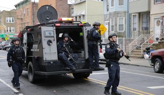FILE - In this Dec. 10, 2019, file photo, New York City Police officers arrive on the scene of a fatal shooting in Jersey City, N.J. Jersey City will pause Thursday, Dec. 10, 2020, to mark the one-year anniversary of the bias attack that killed a police officer at a cemetery and three people in a Jewish grocery store. (AP Photo/Seth Wenig)