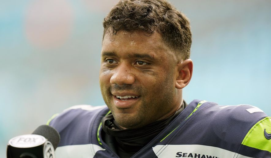 Seattle Seahawks quarterback Russell Wilson (3) talks at the end of an NFL football game, Sunday, Oct. 4, 2020, in Miami Gardens, Fla. Seattle's star quarterback Russell Wilson and Kansas City's standout tight end Travis Kelce are among the 32 finalists for the Walter Payton NFL Man of the Year award. (AP Photo/Wilfredo Lee)