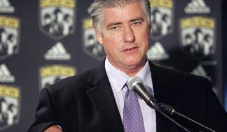 FILE - In this Oct. 20, 2005, file photo, Sigi Schmid talks to reporters after he was hired to be the head coach of the Columbus Crew MLS soccer team in Columbus, Ohio.  Nearly two years after he died, Schmid's presence and influence is being heavily felt heading into Saturday's MLS Cup final between Columbus and Seattle. (AP Photo/Kiichiro Sato, File)