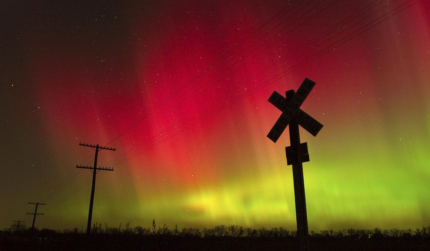 FILE - In this Nov. 8, 2004, file photo, the aurora borealis lights up the sky northwest of Lawrence, Kan. The phenomenon, also called northern lights, occurs when electrically charged particles from the sun enter the earth's atmosphere. Robert Rutledge, of the U.S. government's space weather prediction center said Thursday, Dec. 10, 2020, that stargazers in the continental 48 states have very little chance of seeing the northern lights this week despite an initial promising forecast. (Scott McClurg/The Lawrence Journal-World via AP, File)