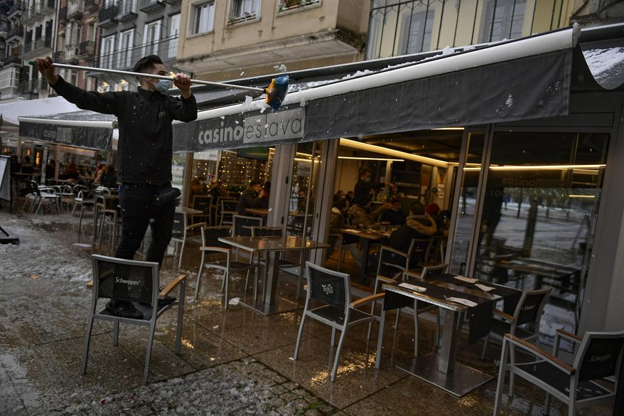 A worker wearing a face mask clears snow from the roof of a bar, in Pamplona, northern Spain, Saturday, Dec. 5, 2020. (AP Photo/Alvaro Barrientos)