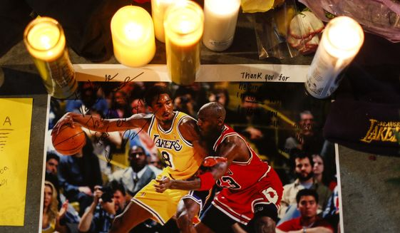 A picture of Kobe Bryant and Michael Jordan is played at a memorial for Bryant in front of Staples Center Jan. 28, 2020, in Los Angeles. Bryant, the 18-time NBA All-Star who won five championships and became one of the greatest basketball players of his generation during a 20-year career with the Los Angeles Lakers, died in a helicopter crash on Jan. 26. (AP Photo/Ringo H.W. Chiu, File) **FILE**