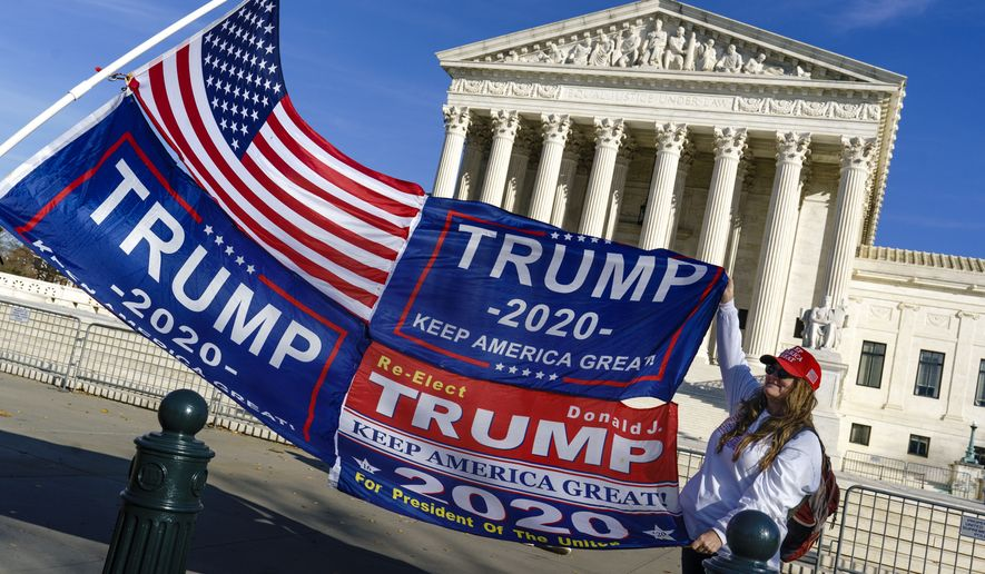 Kathy Kratt of Orlando, Fla., displays her Trump flags as she and other activists demonstrate their support for President Donald Trump at the Supreme Court in Washington, Friday, Dec. 11, 2020. (AP Photo/J. Scott Applewhite)