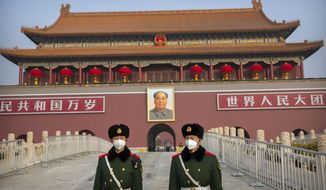 FILE - In this Jan. 27, 2020, file photo, paramilitary police wear face masks as they stand guard at Tiananmen Gate adjacent to Tiananmen Square in Beijing. U.S. financial news service Bloomberg said Friday, Dec. 11, 2020, that Chinese authorities have detained one of its Beijing-based news assistants on what they said was suspicion of endangering national security. (AP Photo/Mark Schiefelbein, File)