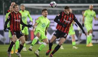 Wolfsburg's Maximilian Philipp and Frankfurt's Stefan Ilsanker, right, battle for the ball during the Bundesliga soccer match between Wolfsburg and Eintracht Frankfurt at Volkswagen Arena in Wolfsburg, Germany, Friday Dec. 11, 2020. (Swen Pf'rtner/dpa via AP)