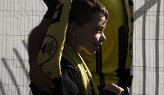 A child is wrapped in his father's Beitar Jerusalem FC soccer scarf during a team training session in Jerusalem, Friday, Dec. 11, 2020, days after the club announced that an Emirati sheikh has purchased a 50% stake in the team. Fans of the soccer club long associated with anti-Arab racism gathered Friday in a show of support for an Emirati businessman's purchase of a stake in the organization, welcoming it as a sign of change even as a smaller number of fans protested the move. (AP Photo/Maya Alleruzzo)