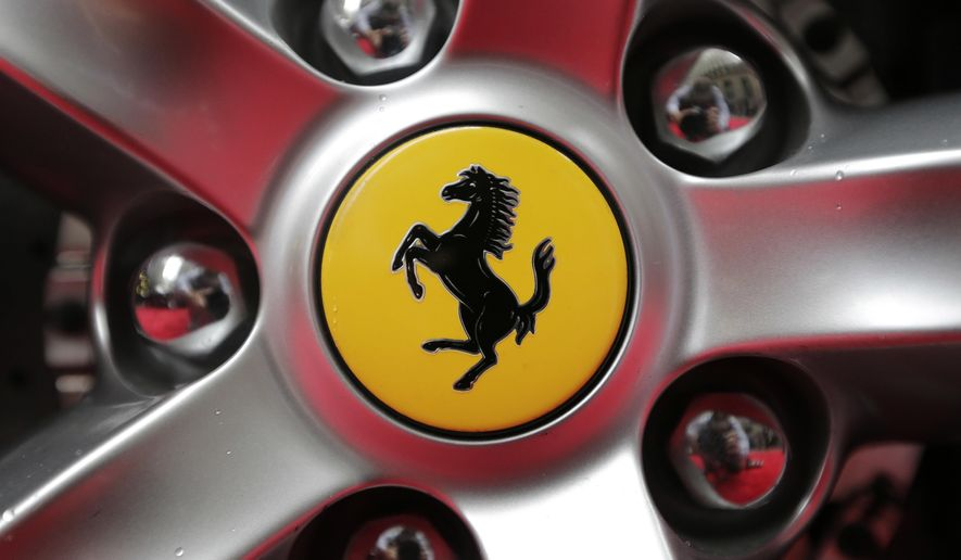 FILE - This Monday, Oct. 9, 2017 file photo shows a Ferrari logo on a car outside the New York Stock Exchange in New York. Luxury sportscar maker Ferrari says its chief executive, Louis Camilleri, has resigned for personal reasons. Chairman John Elkann will take over until a successor is named, Ferrari said in a statement late Thursday, Dec. 10, 2020. (AP Photo/Seth Wenig, File)