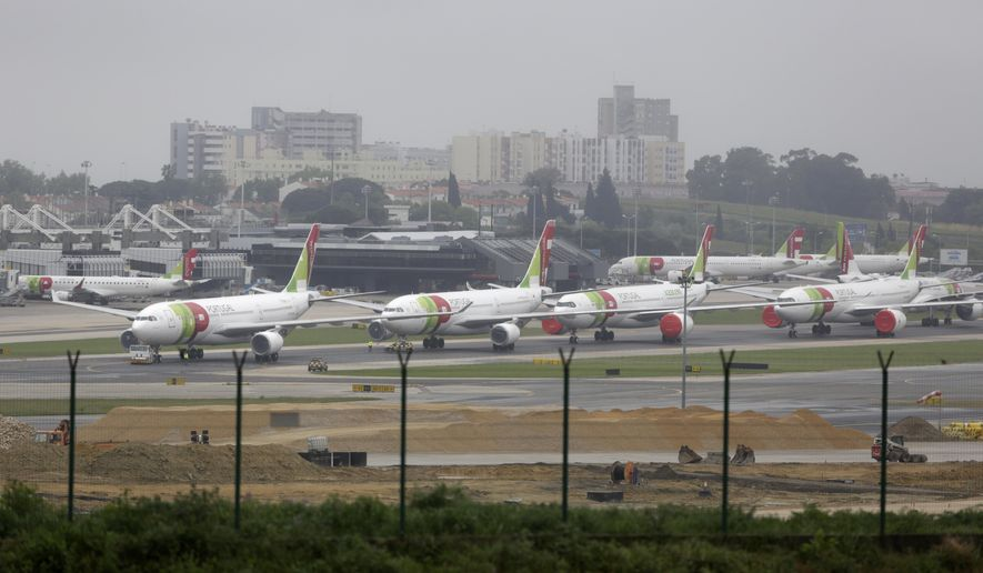 FILE - In this April 9, 2020 file photo, TAP Air Portugal airplanes are parked idle at Lisbon airport. Portugal's government unveiled Friday, Dec. 11, 2020, a 3-billion-euro ($3.6 billion) rescue package for national airline TAP Air Portugal. The plan, which requires the consent of European Union authorities, includes axing more than 3,500 jobs and a 25% payroll cut through wage reductions. (AP Photo/Armando Franca, File)