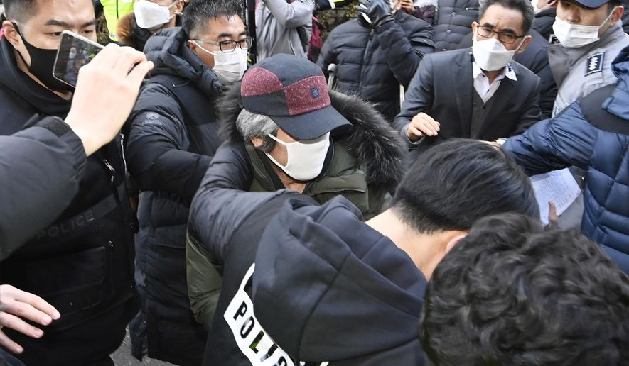 Cho Doo-soon, center, escorted by police officers, arrives home in Ansan, South Korea, Saturday, Dec. 12, 2020. Angry protesters threw eggs and shouted insults as Cho, one of South Korea's most notorious child predators, was released from a prison in southern Seoul on Saturday at the end of a 12-year term. (Kim Jong-taek/Newsis via AP)