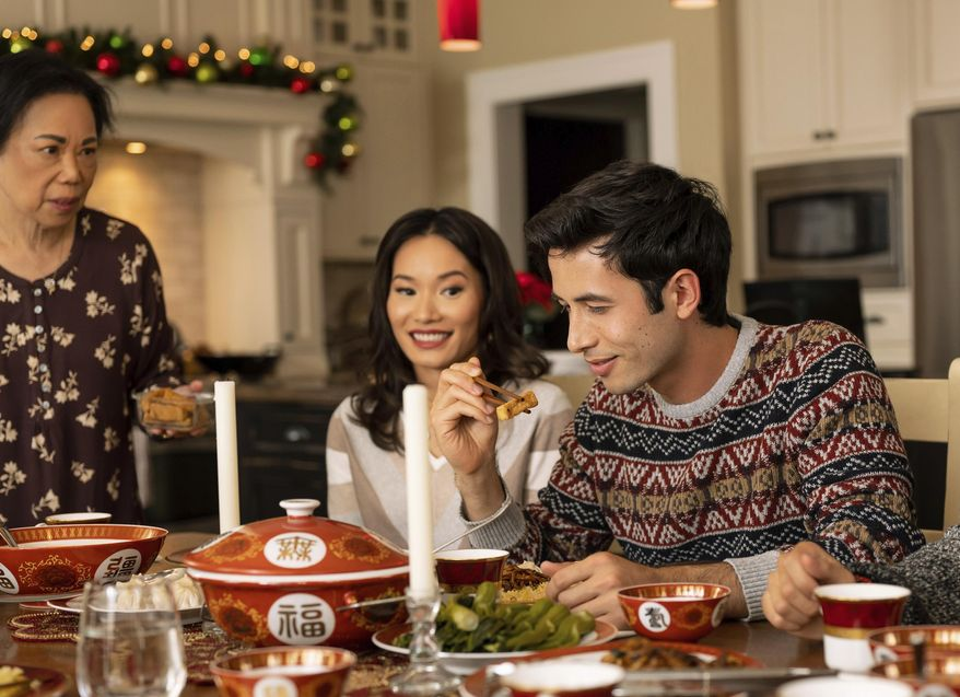 """This image released by Lifetime shows Jacky Lai, center, and Tony Giroux, right, in a scene from """"A Sugar & Spice Holiday."""" The TV film, featuring a mostly Asian cast, premieres Sunday, Dec. 13 at 8pm ET/PT. (Kailey Schwerman/Lifetime via AP)"""