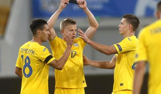 Ukraine's Olexandr Zinchenko, centre, celebrates with teammates after scoring his side's second goal during the UEFA Nations League soccer match between Ukraine and Switzerland at the Arena Lviv stadium in Lviv, Ukraine, Thursday, Sept. 3, 2020. (AP Photo/Efrem Lukatsky)