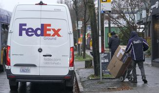 A driver with FedEx carries a package away from a van, Tuesday, Dec. 8, 2020, in Seattle. Store are warning online shoppers that if holiday purchases aren't made soon, they may not be delivered in time for Christmas. (AP Photo/Ted S. Warren)
