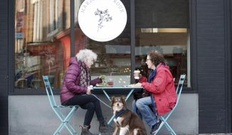 Lenora Kahn, her dog Bella, and Judith Albert dine outside of Marjoram Roux on Railroad Street in Great Barrington, Mass., Friday, Dec. 11, 2020. Even as the weather gets chilly, outdoor dining is safer than dining indoors at a restaurant. (Ben Garver/The Berkshire Eagle via AP)