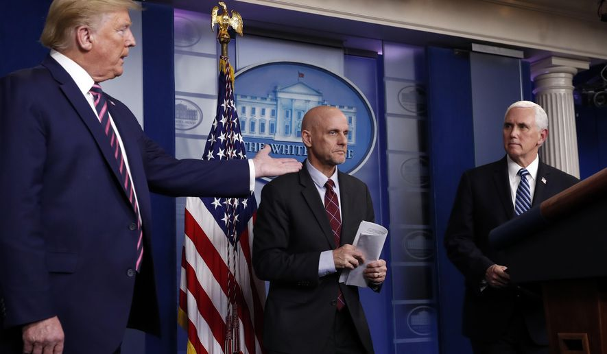 FILE - In this April 24, 2020, file photo, President Donald Trump gestures to Vice President Mike Pence as Dr. Stephen Hahn, commissioner of the U.S. Food and Drug Administration, steps back to the podium to answer a question during a briefing about the coronavirus in the James Brady Press Briefing Room of the White House in Washington. White House chief of staff Mark Meadows has pressed Hahn to grant an emergency use authorization for Pfizer's coronavirus vaccine by the end of the day on Dec. 11. (AP Photo/Alex Brandon, File)