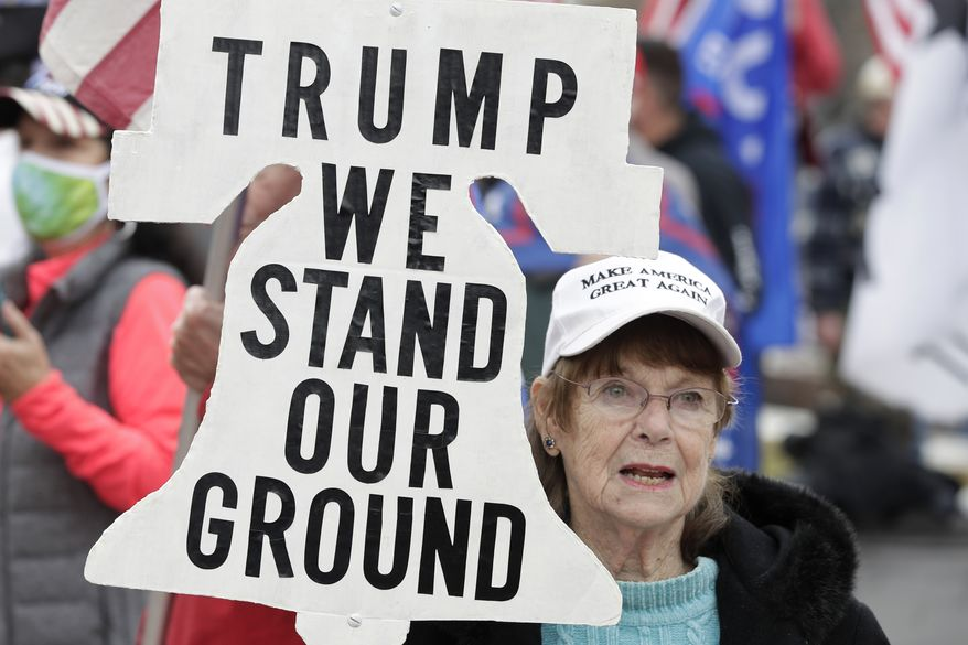 A supporter of President Donald Trump attends a rally at Freedom Plaza, Saturday, Dec. 12, 2020, in Washington. (AP Photo/Luis M. Alvarez)