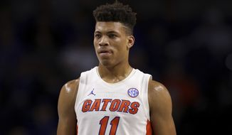 FILE - In this Nov. 29, 2019, file photo, Florida forward Keyontae Johnson (11) looks on during during the first half of an NCAA college basketball game against Marshall in Gainesville, Fla.  Johnson, the Southeastern Conference's preseason player of the year, collapsed coming out of a timeout against rival Florida State and needed emergency medical attention Saturday, Dec. 1`2, 2020. He was taken off the floor on a stretcher and rushed to Tallahassee Memorial for evaluation. The Gators had no immediate update on his condition. (AP Photo/Matt Stamey, File)