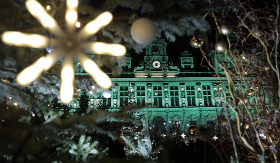 The Paris town hall gets green lightings to celebrate the fifth anniversary of the international pact aimed at curbing global warming, Saturday, Dec.12, 2020 in Paris. Heads of state and government from over 70 countries took part in the event  hosted by Britain, France, Italy, Chile and the United Nations  to announce greater efforts in cutting the greenhouse gas emissions that fuel global warming. (AP Photo/Lewis Joly)