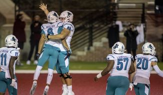 Coastal Carolina wide receiver Jaivon Heiligh (6) and teammate Will McDonald (66) celebrate Heiligh's touchdown against Troy during the second half of an NCAA college football game, Saturday, Dec. 12, 2020, in Troy, Ala. (AP Photo/Vasha Hunt) **FILE**