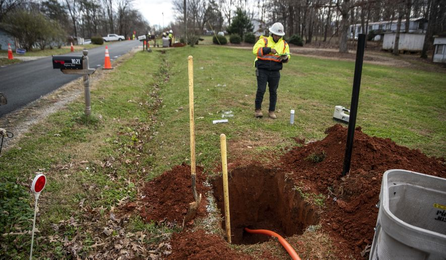A fiberoptic cable is pulled through a hole drilled underground in Amherst, Va., Tuesday, Dec. 1, 2020. The cable will allow rural residents in Amherst and Nelson counties to have access to high-speed internet. County officials are working to resolve online woes of residents and businesses through a broadband expansion effort with the help of companies to have all homes covered with reliable service. (Kendall Warner/The News & Advance via AP)