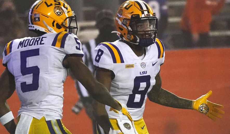 LSU running back Tre Bradford (8) is congratulated by wide receiver Koy Moore (5) after Bradford scored a touchdown during the second half of the team's NCAA college football game against Florida, Saturday, Dec. 12, 2020, in Gainesville, Fla. (AP Photo/John Raoux)